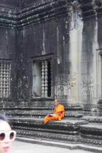 A monk sits inside Angkor Wat